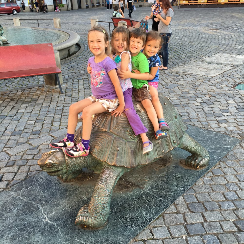 Pioneers Kids hanging out on a turtle