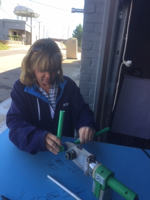 trish heating two ends of aquatherm pipe fittings before fusing them together.