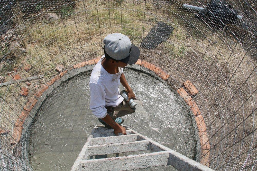 Daniel trabaja para afinar el piso de la cisterna.