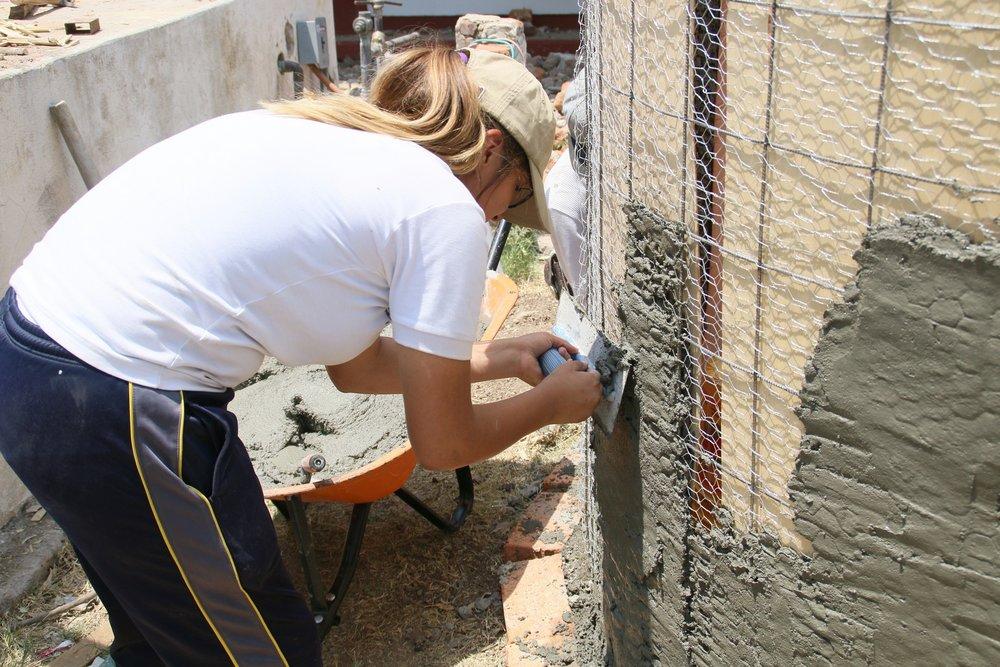Un estudiante aplica cemento a la pared de la cisterna.