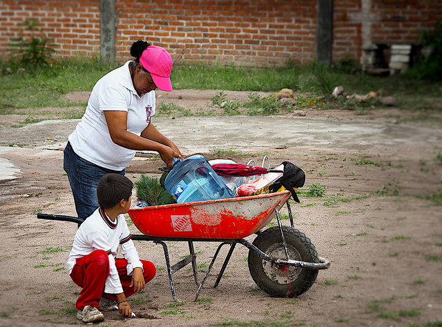Residente de Pozo Hondo lleva agua a casa de la cisterna comunitaria.