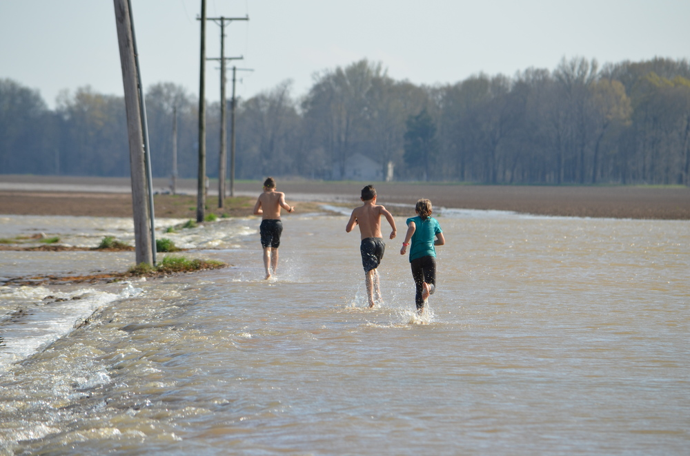 My kids running through the flooded cotton field.  It's hard to imagine anything will be growing here in a few weeks.