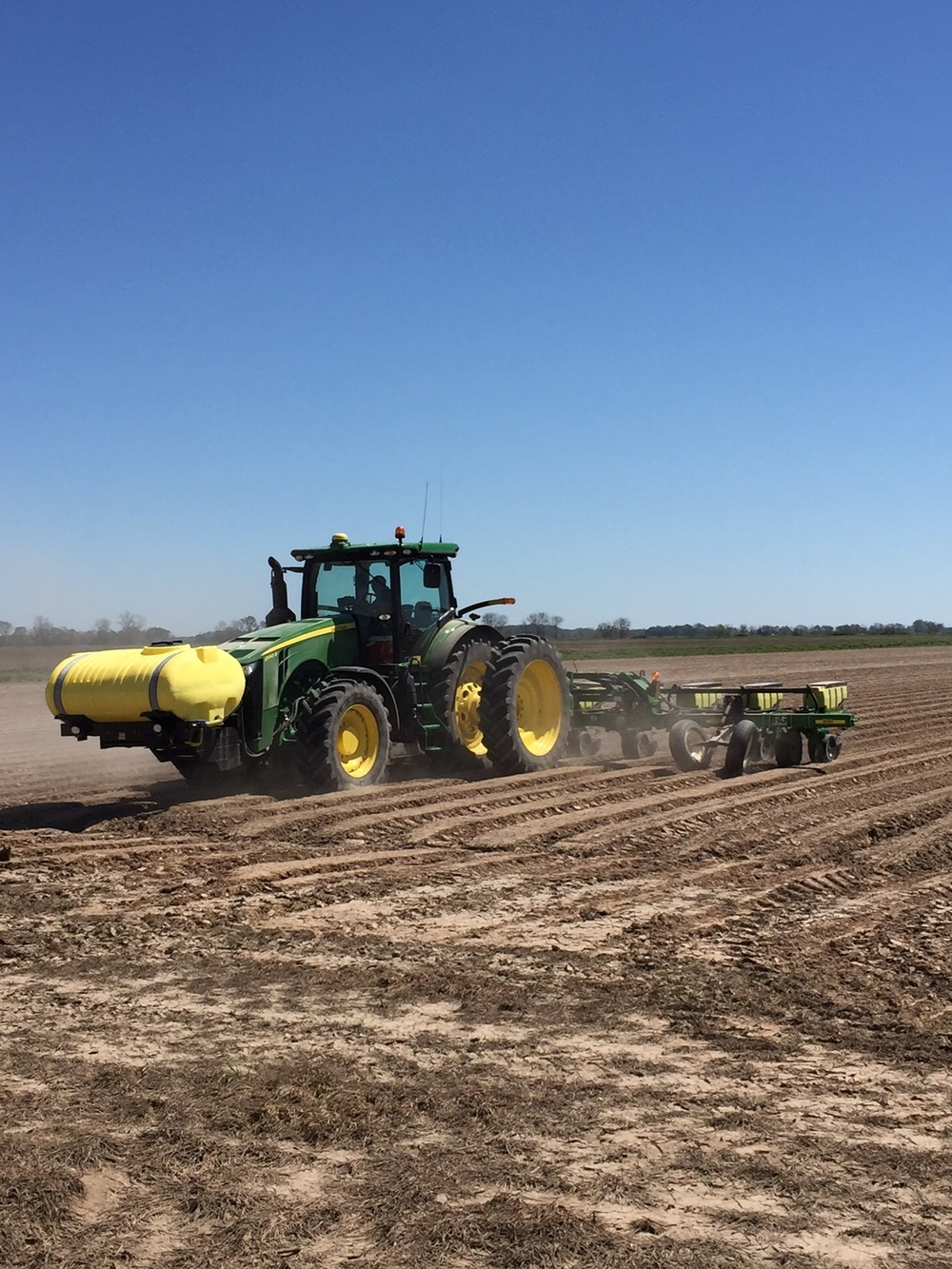 a tractor pulling a planter with cotton seed