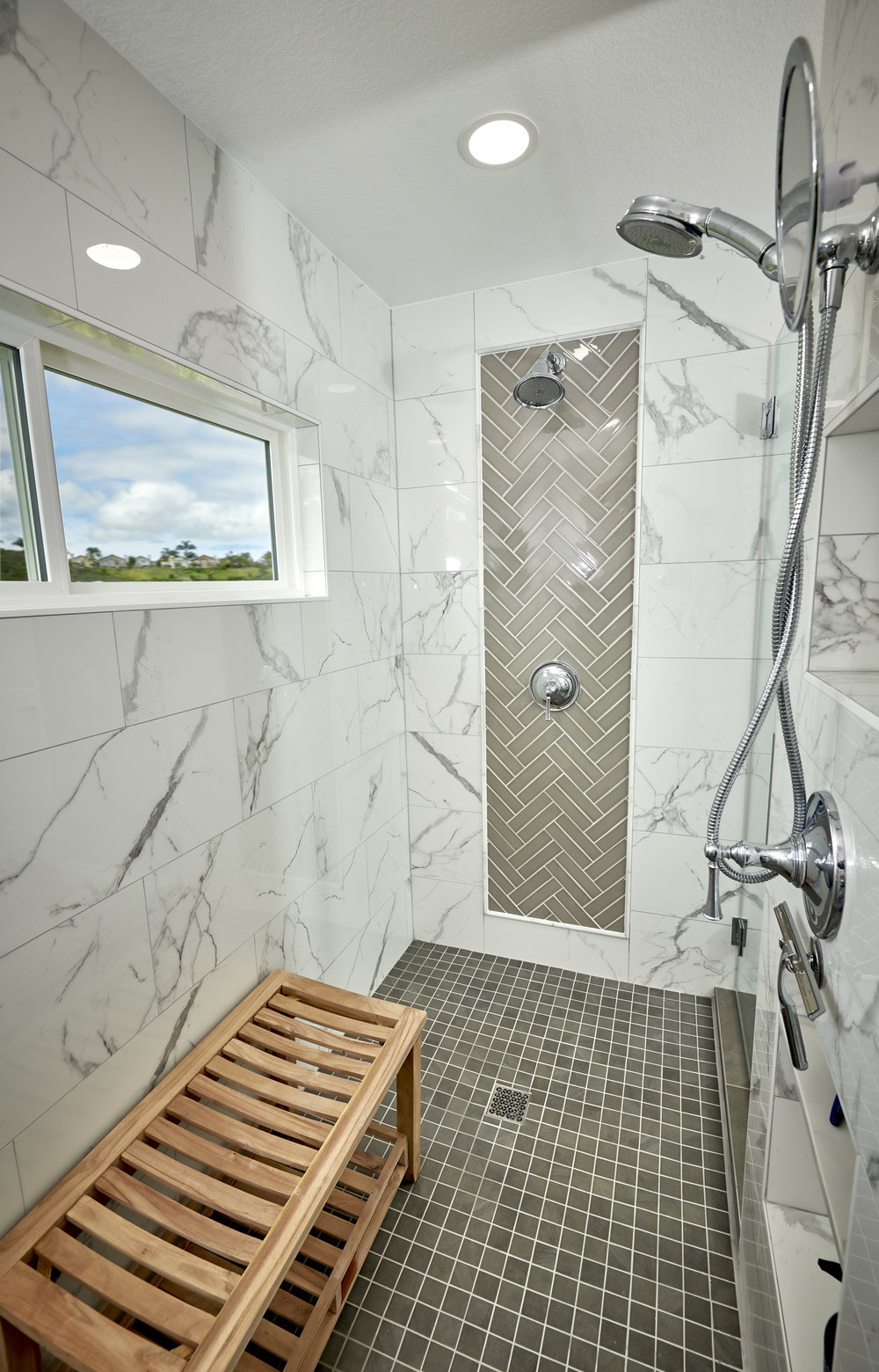 Oversized shower porcelain marble like tile with grey subyway in a chevron pattern