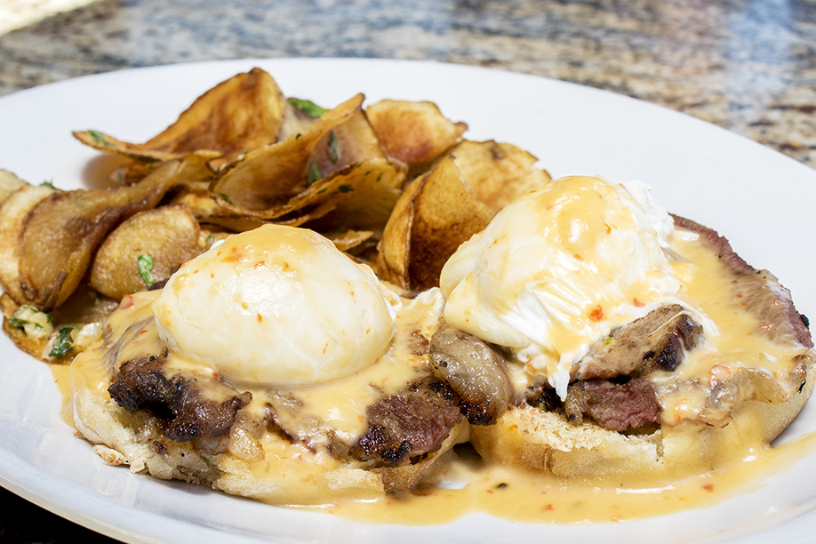Cowboy Benedict - Poached egg, tri-tip and cheese sauce on an English muffin. Side of breakfast potatoes.