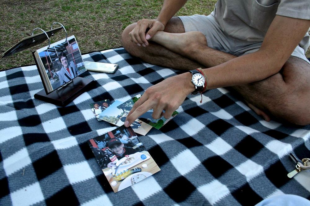 "Josef Rinderer looks through family photos at Daley Park in Tempe, Ariz. on April 9, 2016. ""I embrace both sides equally, but I've never truly immersed myself in either of the cultures,"" he said. ""I don't know why. I've really struggled, especially with my mother's side. I embrace the Costa Rican people and the Latino people, that I embrace, but I don't necessarily embrace my family ... It's not that I look down at them, it's the values they hold true to themselves that really bother me."""