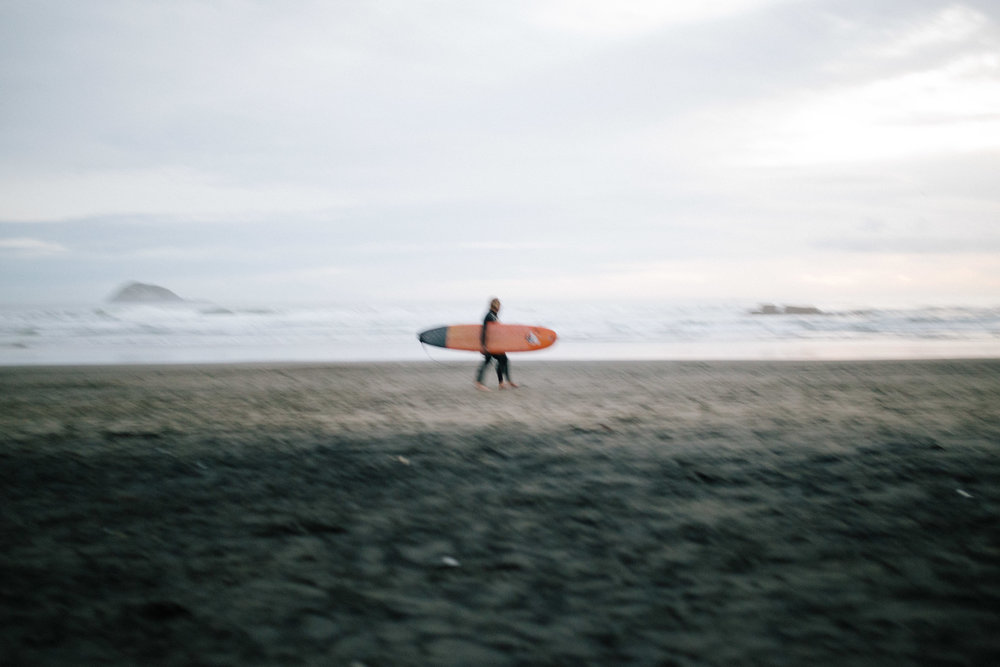 May 9 2017  A surfer leaves Murawai Beach at sunset, where my cousin and I sat watching the waves roll in Auckland, New Zealand.