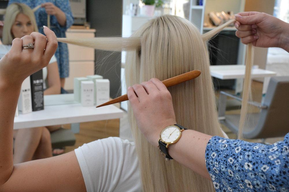 Prep håret med tekstur-spray og tupper på kronen og skill for å få mer volum.  Plukk ut hår noen cm rett over øret på hver side og fest med en liten gummistrikk bak.