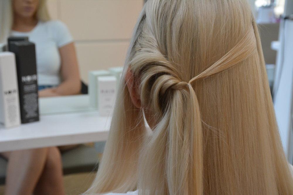 Sett bort håret fremfor øret.  Start med håret rett bak øret og tvinn litt og litt av håret rundt hårstrengen bakover.