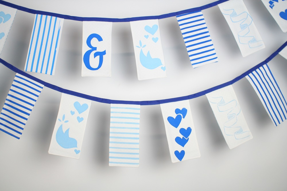 10.6 metres hand sewn and hand screen printed rectangular bunting:   Flags measure 21 cm x 9 cm  Flags are backed with pale blue polka dot cotton.   HIRE:   £3.5 per metre    BUY:   £12 per metre