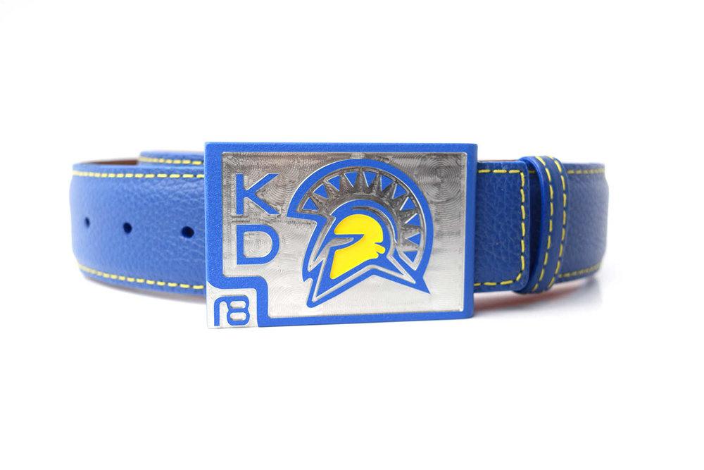 Custom San Jose State Belt - Blue textured powder with raised logo (embossed) and yellow gloss enamel. Premium blue pebble grain calfskin leather belt strap with yellow threading.