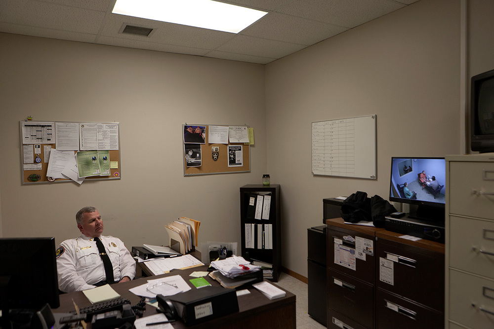"7:21 PM  - Scott County Sheriff Rick Walter watches as the suspect is interrogated via a closed circuit video feed from a detective's desks. Sheriff Walter said 90% of his department's resources were used during the investigation, arrest and interrogation that day.  Read Alan Schwarz's story in The New York Times ""Missouri Alone in Resisting Prescription Drug Database"""