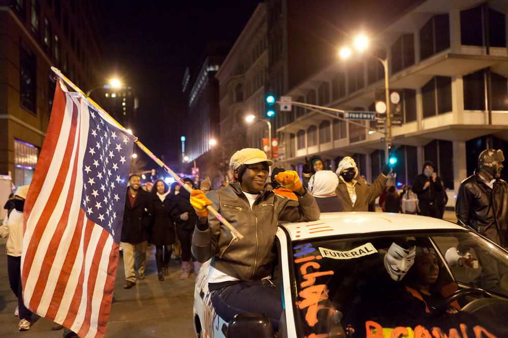 "A protester smiles as she rides in the ""Mike Mobile"" in front of protesters on Washington Ave."