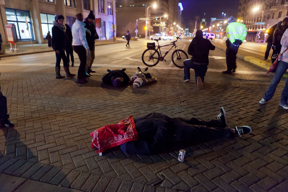 "A protester lays on the street during a ""die in"" as police cars block traffic a block away."