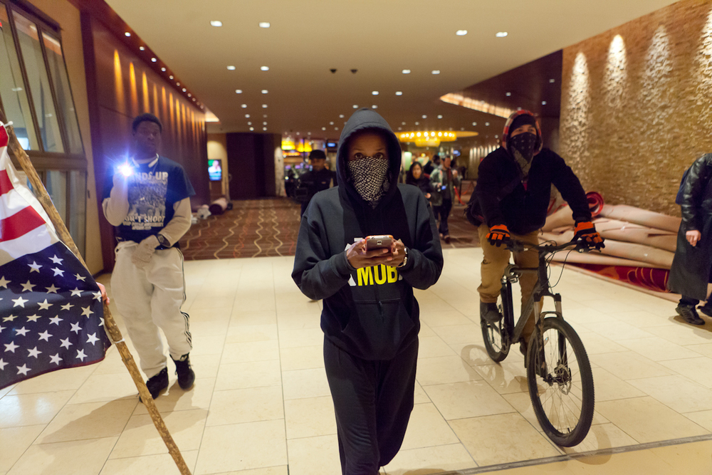 Protesters walk (and ride) on their way out of the casino after chanting protests at the edge of the casino floor.