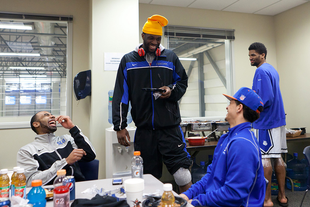 Kwamain Mitchell (left) laughs at teammate Corey Remekun's floppy yellow hat' as Dwayne entered a rare but informal / casual team dinner. The team seemed to be tired from a day on the road and a little slap happy. At moments the room erupted in slap happy laughter and then focused on ESPN's coverage of their own team as well as a reverence for Duke.