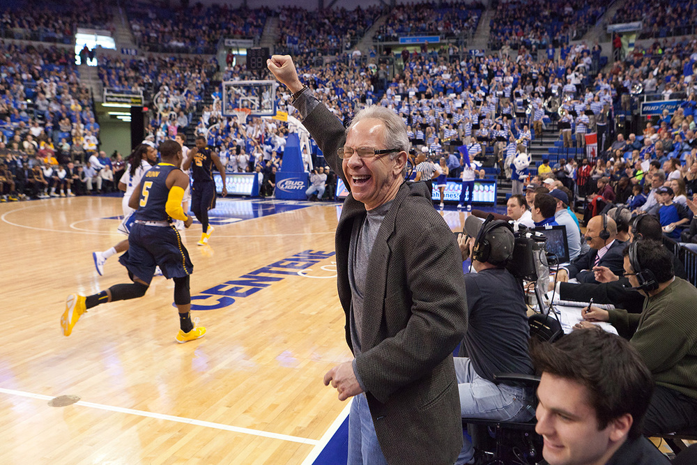 "Dr. Richard A. Chaifetz pumps his fist as as the SLU Billiken basketball team plays against LaSalle. They call him their ""Super Fan"". He donated $12 million to SLU and they names the arena after him. Now he can be found court side at most games."