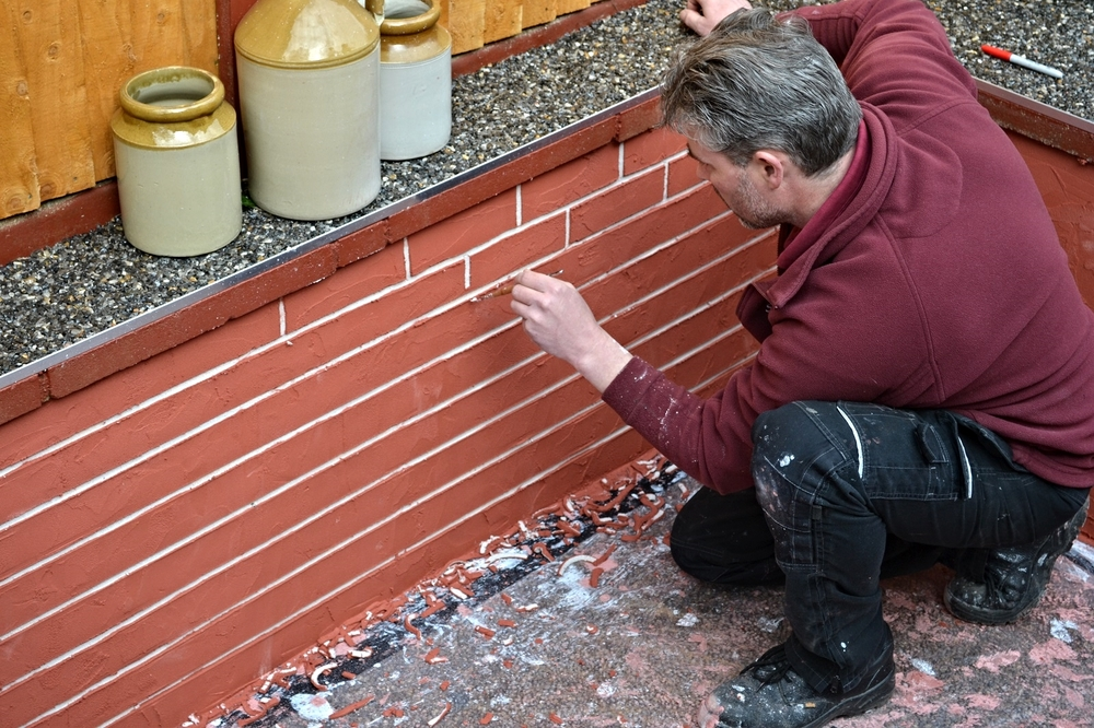 After the render has been applied to the wall, the mortar lines are 'cut' through the top coat to create the brick effect