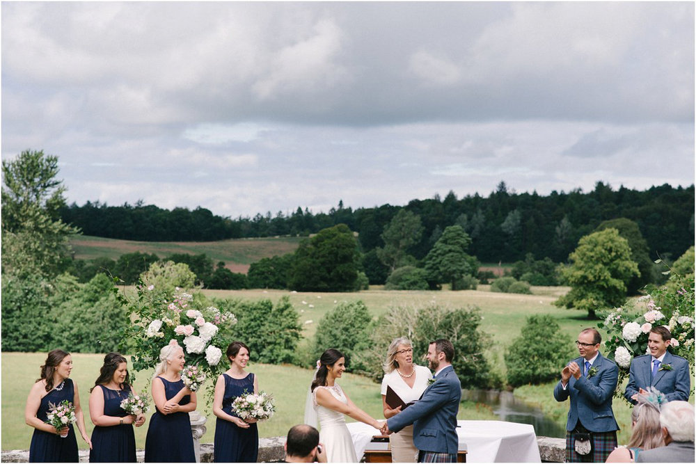 Summer Scottish castle wedding ceremony outdoors with bridesmaids in navy dresses and groomsmen in blue kilts in front of Blairquhan castle by Cro & Kow Photography