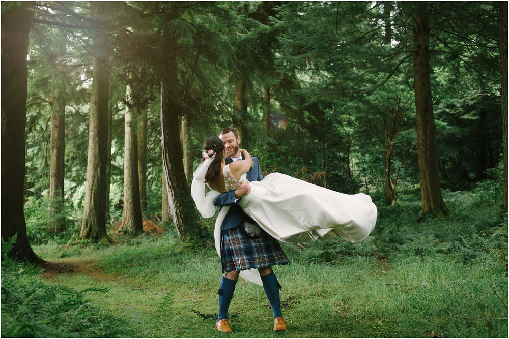 Groom lifts the bride in his arms in a forrest near Blairquhan castle in Scotland by Cro & Kow