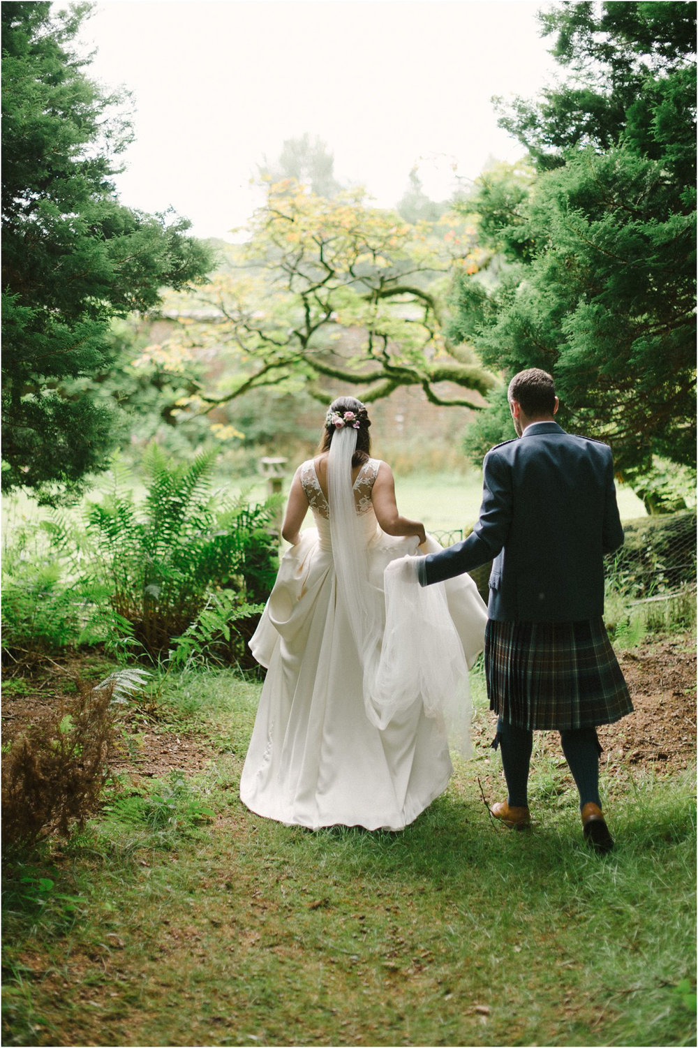Bride and groom in kilt walking away in a forrest near Blairquhan castle in Scotland by Cro & Kow