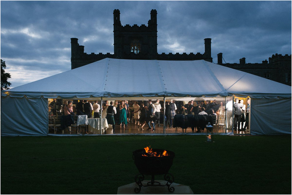 A lit marquee with translucent windows at dusk with a Scottish castle of Blairquhan during a summer wedding ceilidh dancing by Cro & Kow