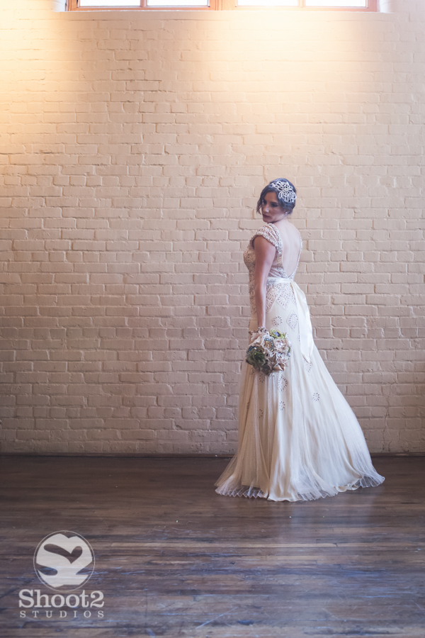 bride by brick wall