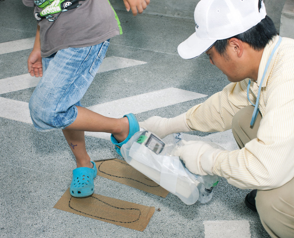 A boy gets tested for radioactive contamination by a Hokuriku Nuclear Power Plant worker
