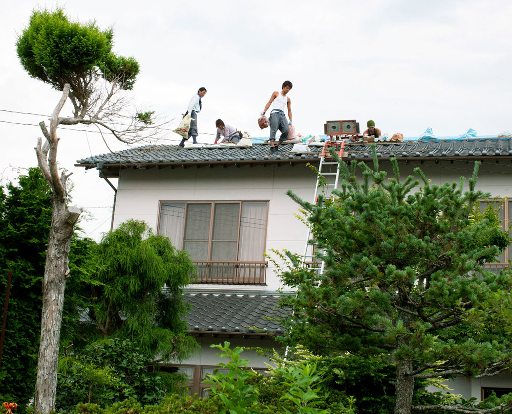 Family in Minamisoma fixing their roof which was damaged by earthquake