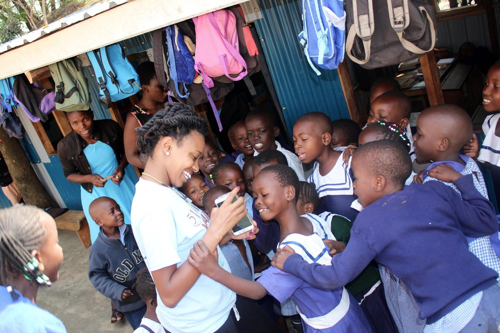 Chandell Stone, President of Destination Teach, interacts with children from the school during a break from class.