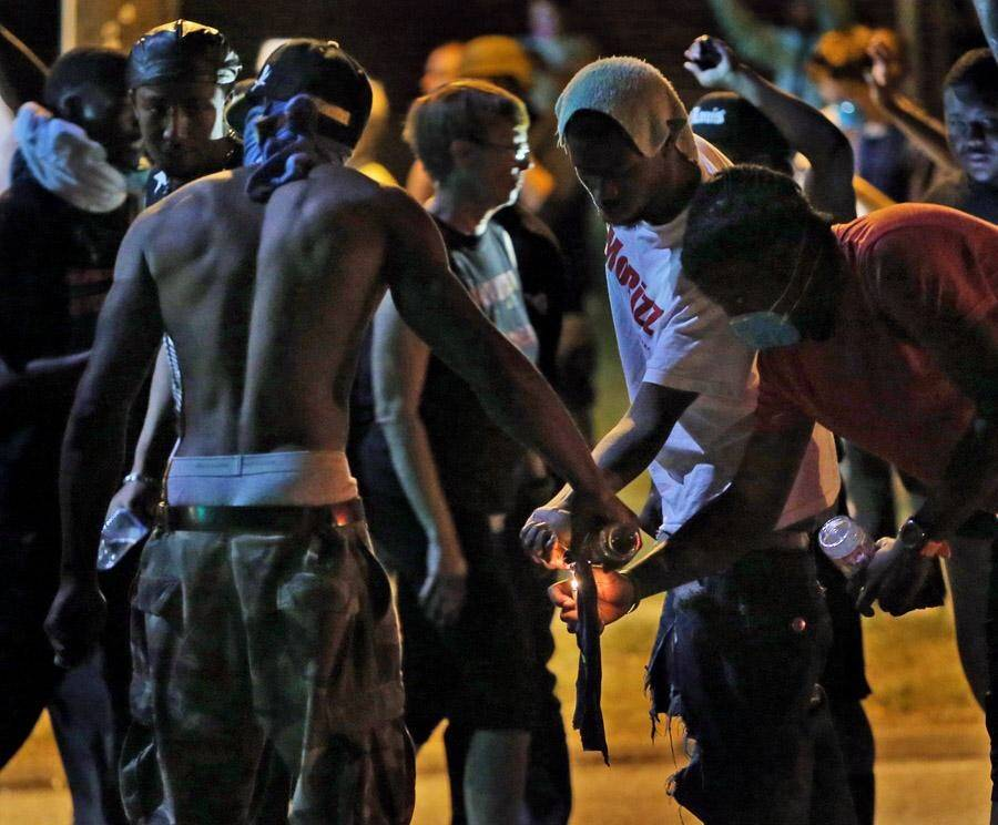 Young protestors lighting and preparing to launch a Molotov cocktail at Ferguson police