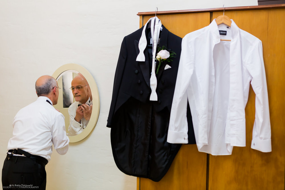 father getting ready in mirror for sons wedding in Malta