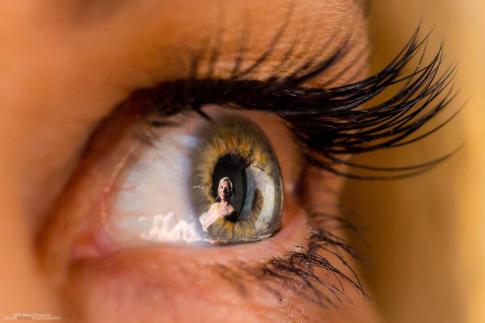 creative wedding day photo of the bride reflected in the eye of her mother