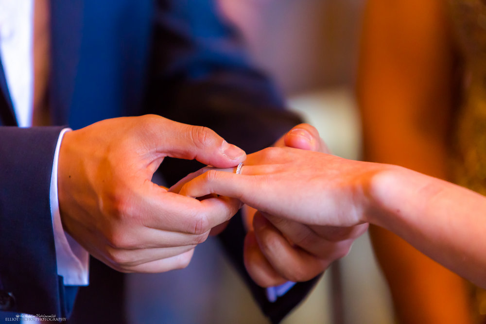 groom puts bride's wedding ring on her finger during the wedding ceremony