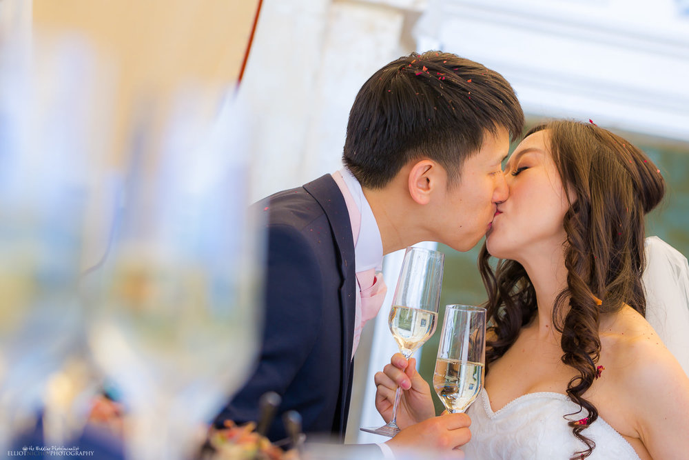 bride and groom steal a champagne kiss