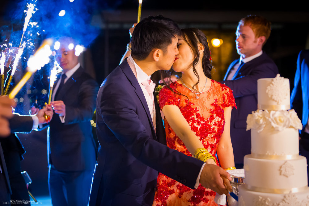 Bride and groom kiss while cutting their wedding cake