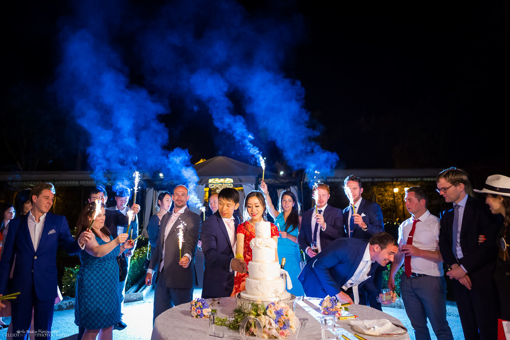 cutting of the wedding cake with flares