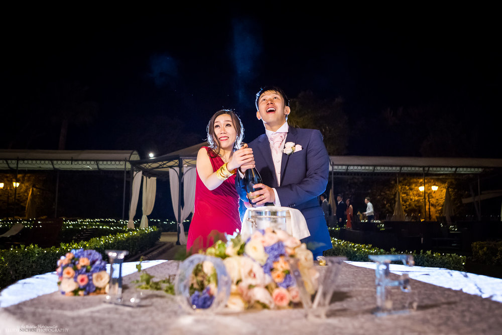 Bride and groom open a bottle of Champagne