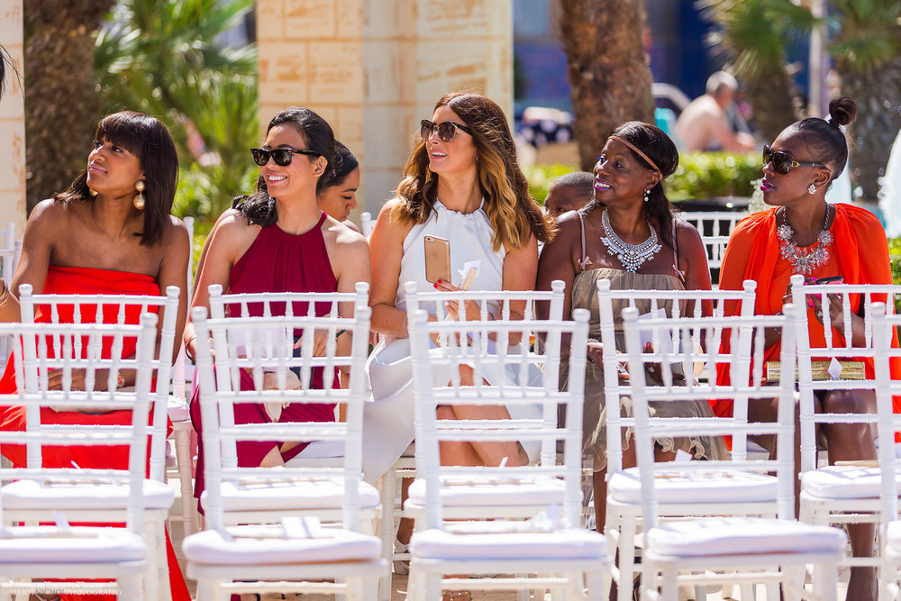 female wedding guests taking their seats at the wedding ceremony at the Hilton, Malta