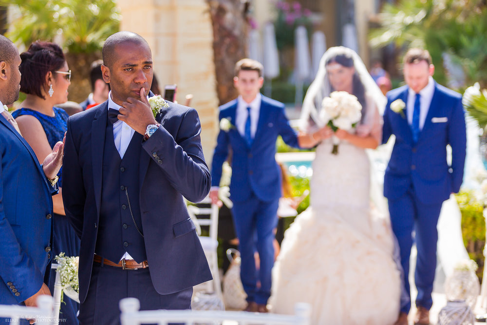 emotional groom as his future wife walks up the aisle in an outdoor wedding ceremony