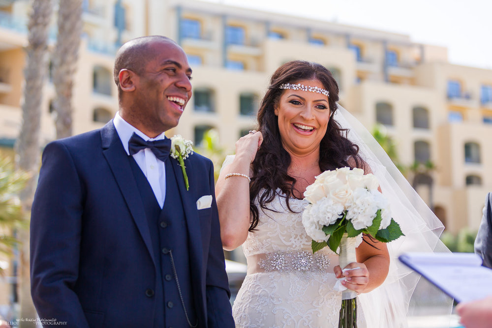 Bride and Groom laughing during the wedding ceremony at the Hilton, Malta
