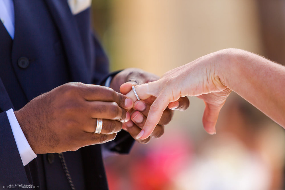 Grooms puts on the wedding ring on his brides finger during the wedding ceremony