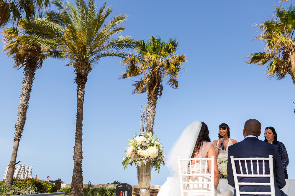 Reading during the wedding ceremony under the palm trees