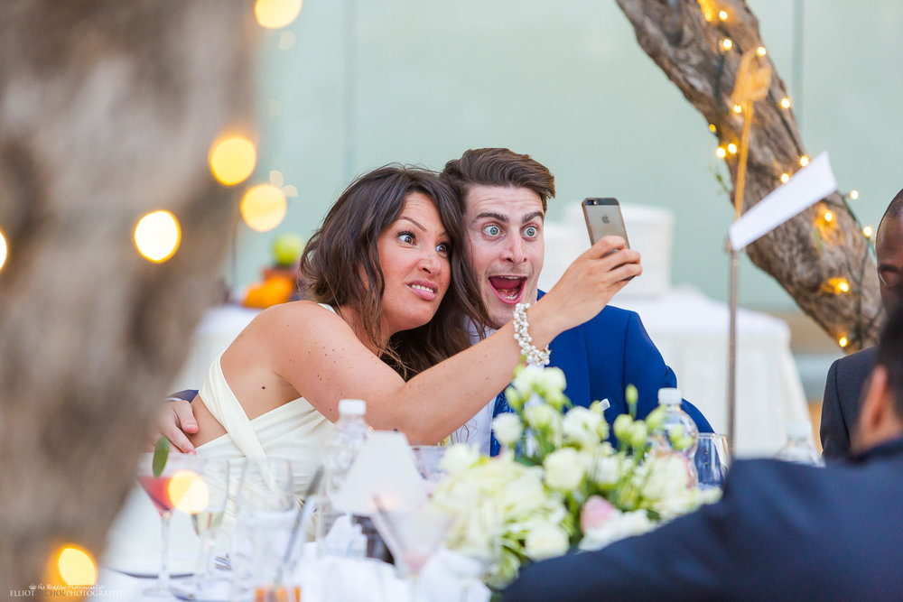 wedding guests pulling funny faces while taking selfies