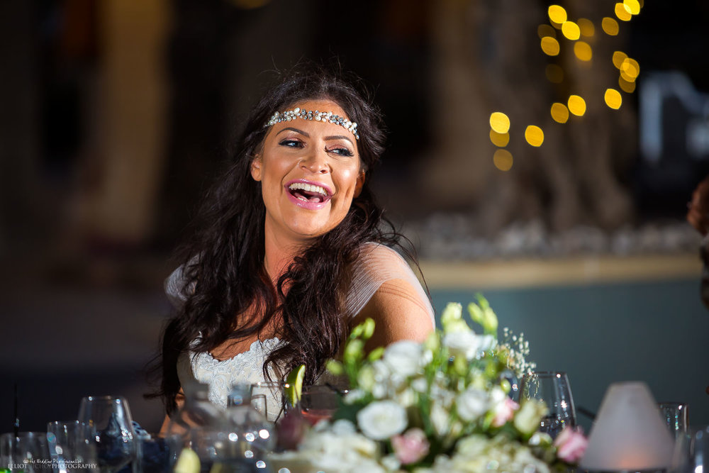 bride laughing during the wedding reception speeches