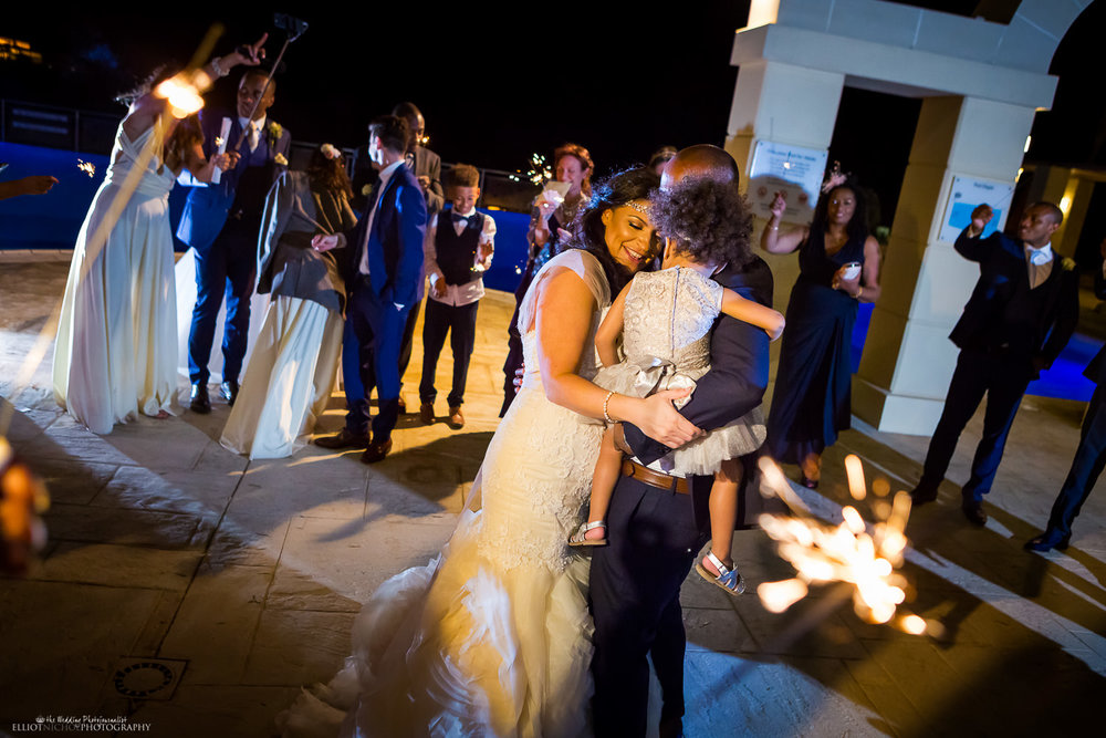 Bride and groom have their first dance with their daughter and surrounded but guests and sparklers