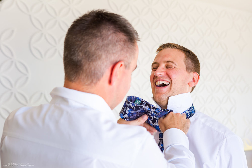 groom laughing with his best man while having his tie tied