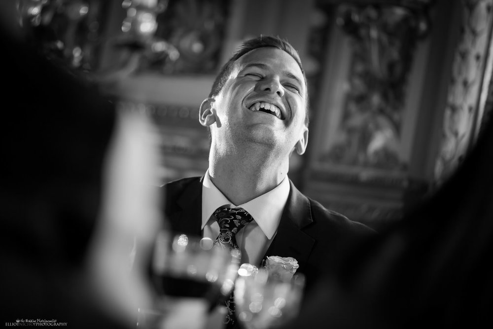 groom laughing during the wedding reception speeches