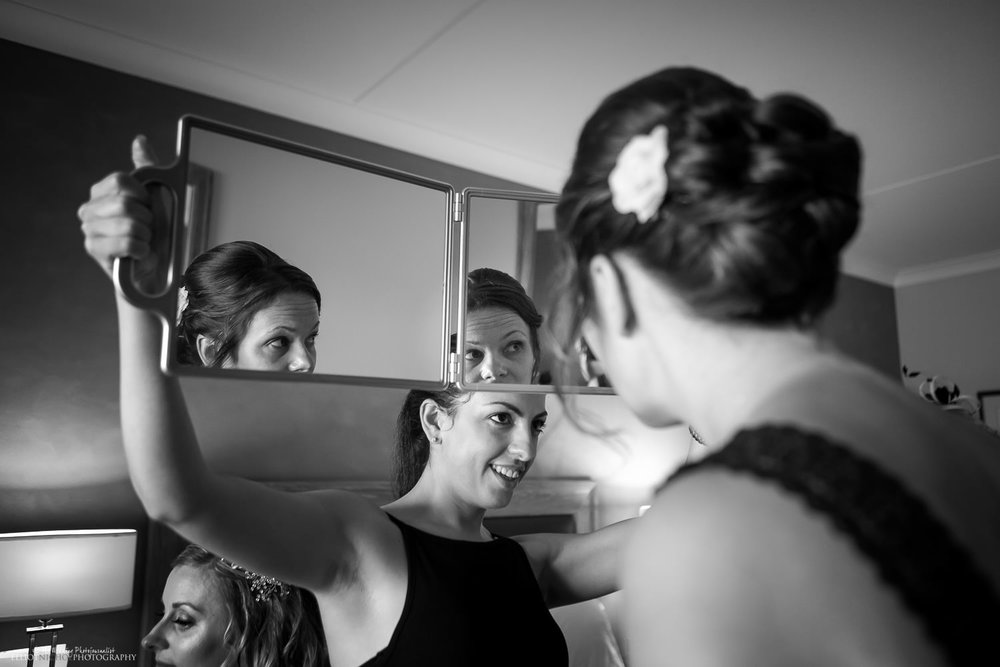 Hair stylist shows bridesmaid her finished hair for the wedding day.