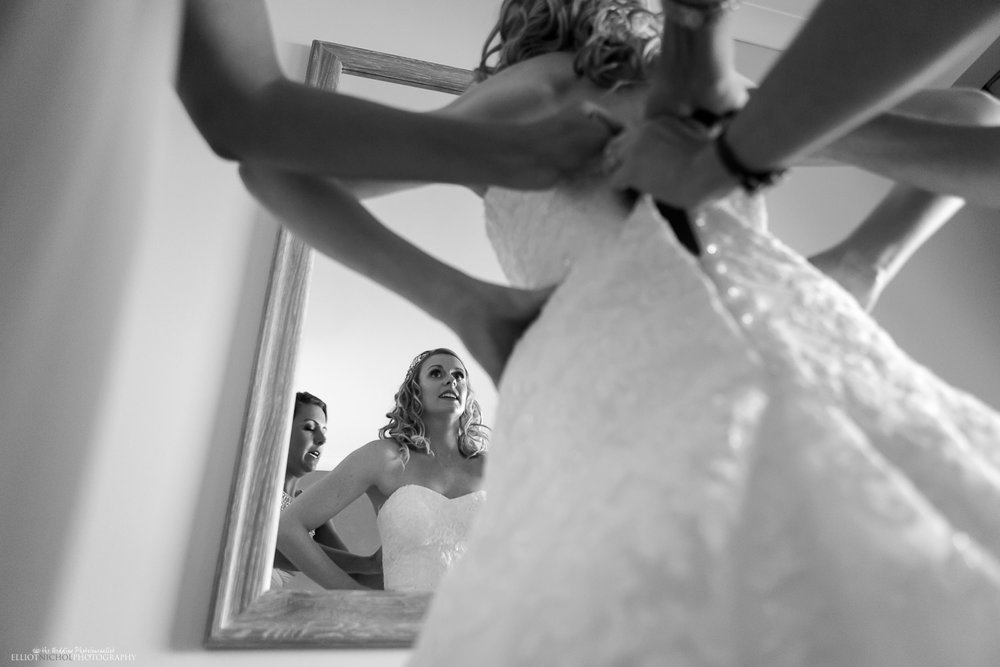Bridesmaids helping the bride into her wedding dress.